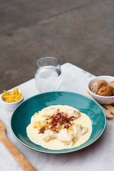 Verse ravioli pasta met witte saus en rauwe cent pasta; spatel op het bureau