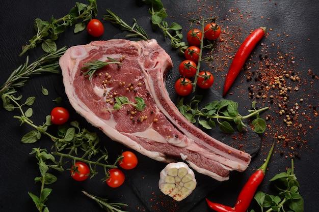 Verse raw beef bone rib steak op zwart bord met kruiden en specerijen