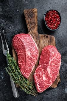 Verse raw top blade of platte ijzeren rundvlees steaks op een slager snijplank