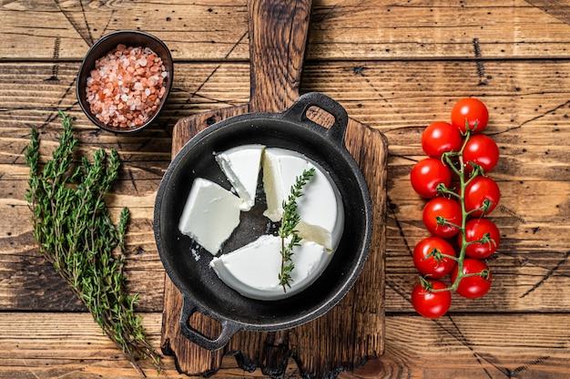 Verse ricotta-roomkaas in een pan met basilicum en tomaat. houten achtergrond. bovenaanzicht.