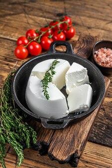 Verse ricotta-roomkaas in een pan met basilicum en tomaat