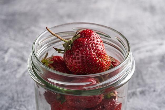 Verse rijpe aardbeienvruchten in glazen pot, zomer vitamine bessen op grijze steen