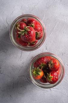 Verse rijpe aardbeienvruchten in twee glazen potten, zomer vitamine bessen op grijze steen