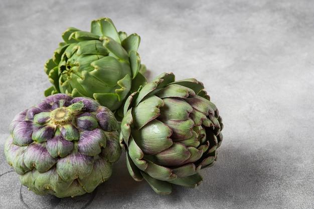Verse rijpe artisjokken bloemen groente op grijs Premium Foto