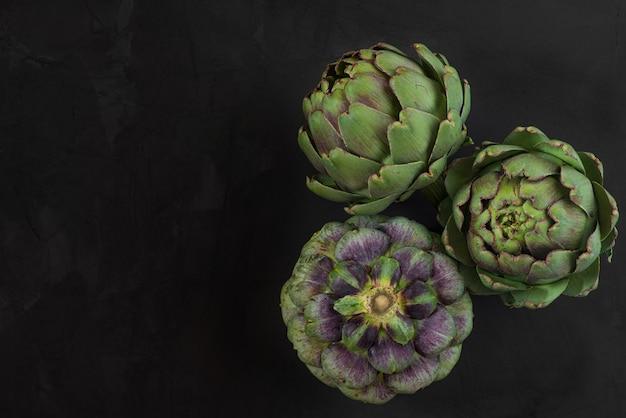 Verse rijpe artisjokken bloemen groente op zwart Premium Foto