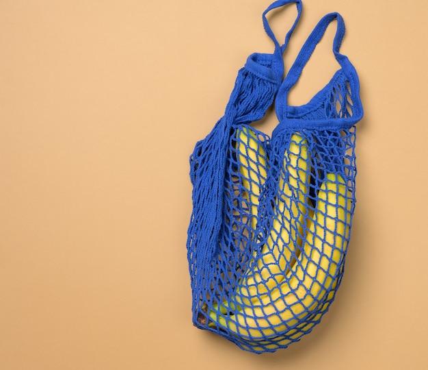 Verse rijpe bananen in een blauwe eco-tas van textiel, bovenaanzicht