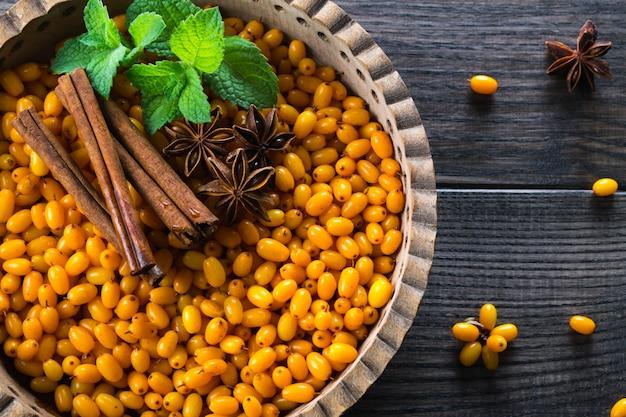 Verse rijpe biologische duindoorn bessen in houten kom met kaneelstokjes, anijs sterren en munt op donkere tafel. ingrediënten voor vitamine gezonde drank