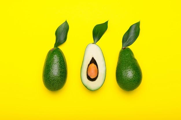 Verse rijpe biologische groene avocado's en halveren met blad op geel