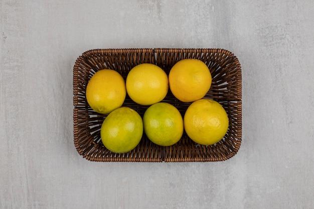 Verse rijpe citroenen op houten mand.
