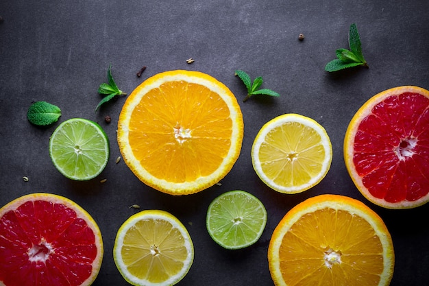 Verse, rijpe citrusvruchten en groene muntblaadjes op donkere achtergrond. gezonde voeding en dieet