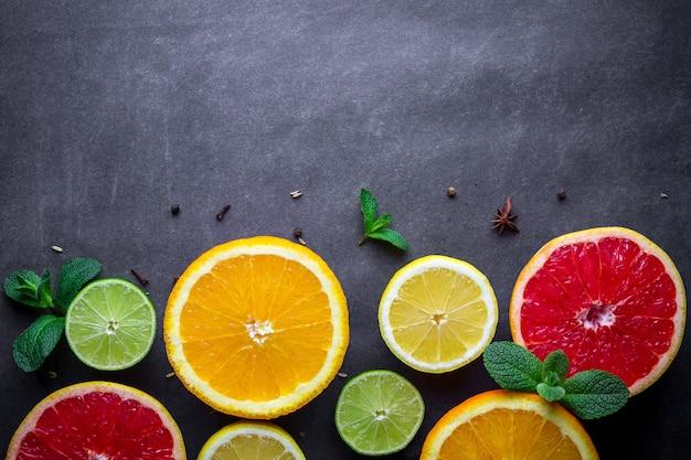Verse, rijpe citrusvruchten en groene muntblaadjes op donkere achtergrond. kopieer ruimte