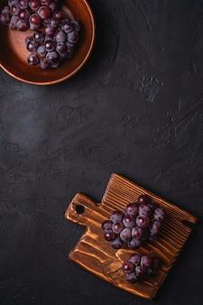Verse rijpe druiven bessen in bruine houten kom en snijplank op donkere stenen achtergrond, bovenaanzicht kopie ruimte