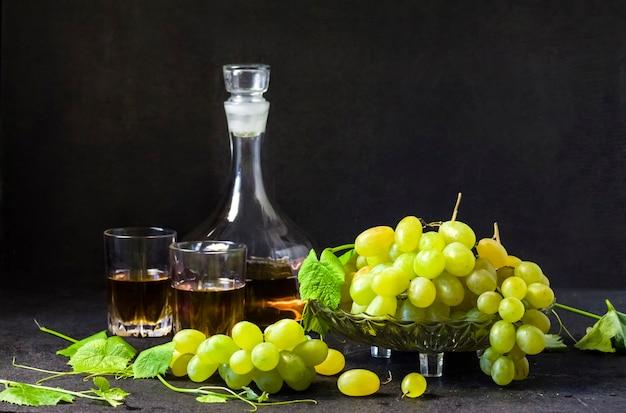Verse rijpe druiven in een fruitschaal en karaf met druivensap op zwarte achtergrond. ruimte kopiëren