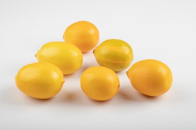 Verse rijpe gele citroenen op witte tafel.