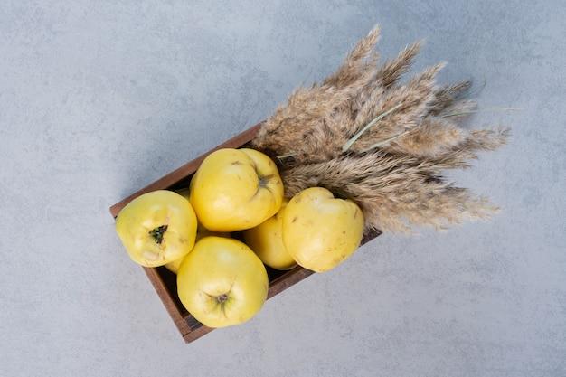 Verse rijpe gele kweepeer. vruchten in een houten kist. bovenaanzicht.