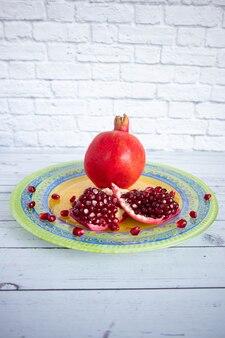 Verse rijpe granaatappel ligt op een heldere mooie plaat. een stuk granaatappel en de zaden worden op een bord gestrooid.