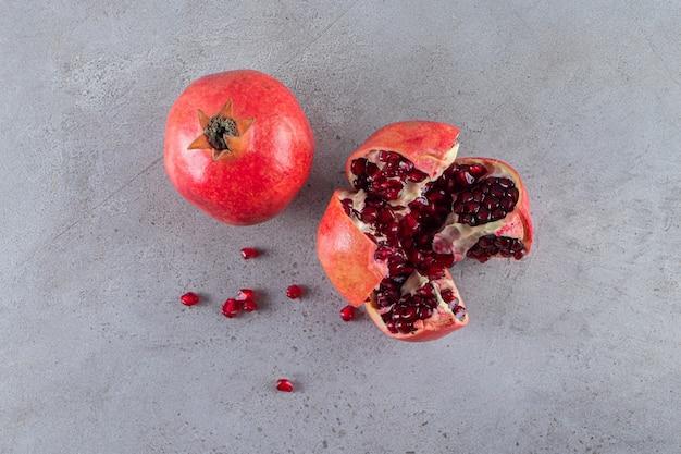 Verse rijpe granaatappels met zaden geplaatst op stenen achtergrond.