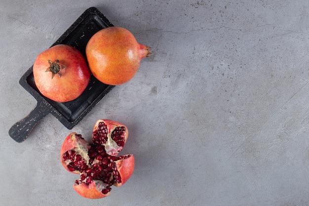 Verse rijpe granaatappels met zaden op een zwarte bord.