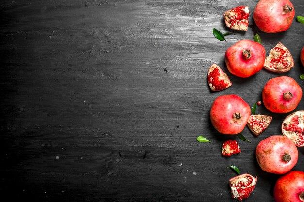 Verse rijpe granaatappels. op het zwarte bord.
