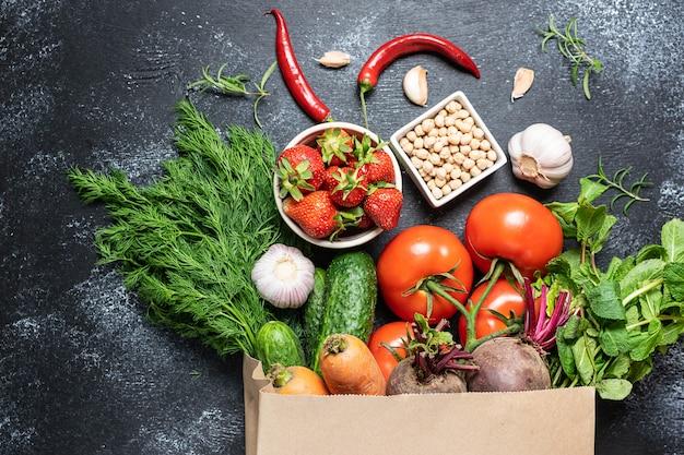 Verse rijpe groenten, fruit en groenen in ambachtelijke papier boodschappentas op zwarte rustieke achtergrond