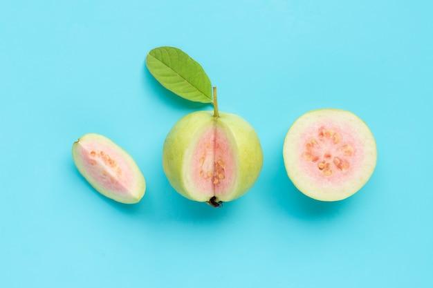 Verse rijpe guave met blad op blauwe achtergrond.