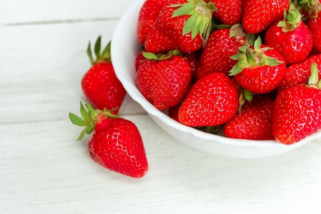 Verse rijpe heerlijke aardbeien in een witte kom op houten oppervlak