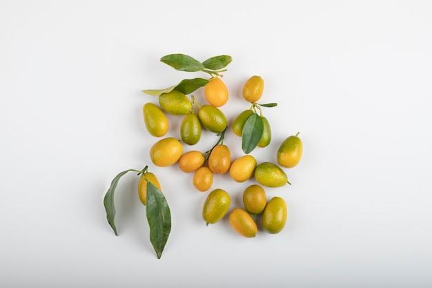 Verse rijpe kumquats met bladeren op witte tafel.