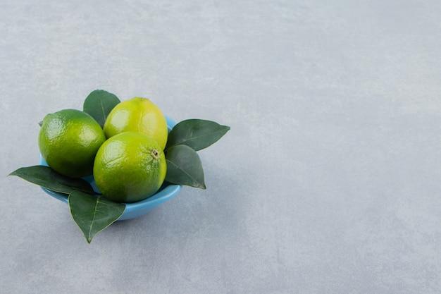 Verse rijpe limoenen in blauwe kom