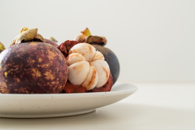 Verse rijpe mangosteenvruchten op witte plaat