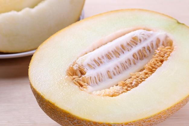 Verse rijpe meloen in een gesneden close-up op een natuurlijke houten tafel