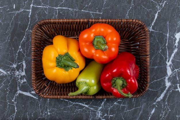 Verse rijpe paprika's in geweven mand.