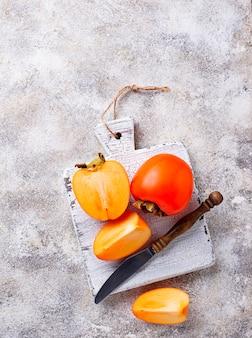 Verse rijpe persimmon op witte snijplank