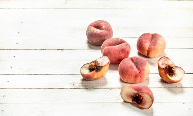 Verse rijpe perziken op een witte houten tafel