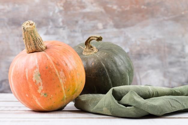 Verse rijpe pompoenen oranje en groen, op een witte houten tafel. gezond dieet. kopieer ruimte.