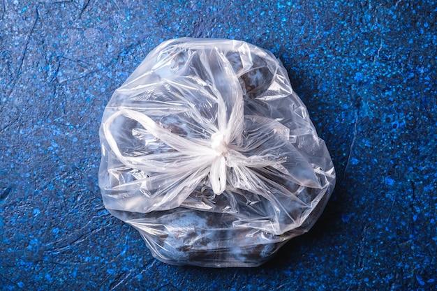 Verse rijpe pruimenvruchten in plastic zakpakket op blauwe abstracte achtergrond, hoogste mening