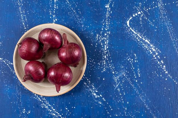 Verse rijpe rode uien geplaatst op keramische plaat