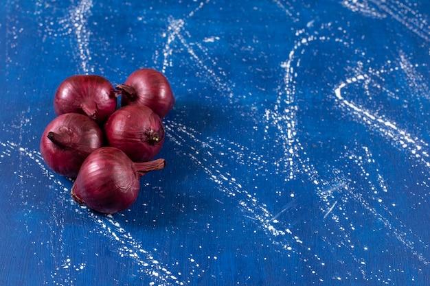 Verse rijpe rode uien geplaatst op marmeren oppervlak