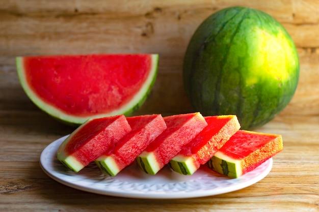 Verse rijpe rode watermeloen. het geheel en in stukjes gesneden op plaat op houten tafel