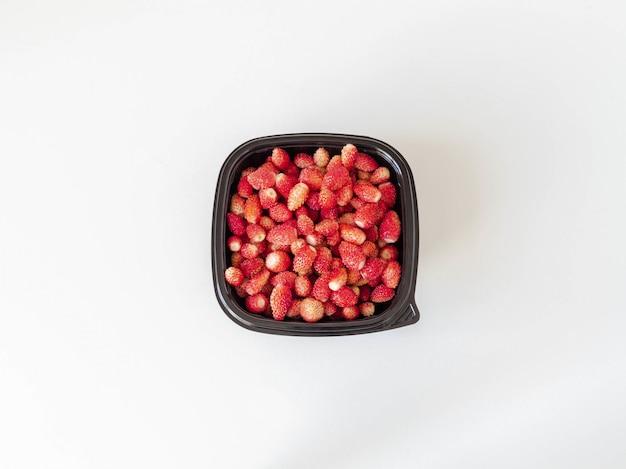 Verse rijpe rode wilde aardbeien in een zwarte plastic container op een witte achtergrond. bovenaanzicht. kopieer ruimte