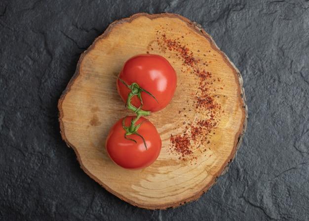Verse rijpe tomaten met rode hete chili peper op een houten bord.