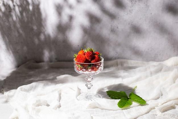 Verse rode aardbeien in een glas in de schaduw van bloemen op een tafel op een betonnen ondergrond.