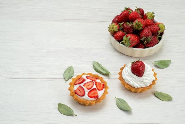 Verse rode aardbeien zachte en heerlijke bessen in witte plaat met taarten op licht