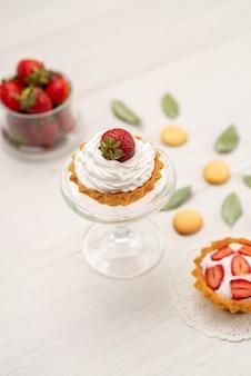 Verse rode aardbeien zachte en heerlijke bessen met taarten en koekjes op licht