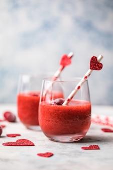 Verse rode aardbeimargarita of daiquiricocktail met harten over grijze achtergrond, valentijnskaartdagconcepten