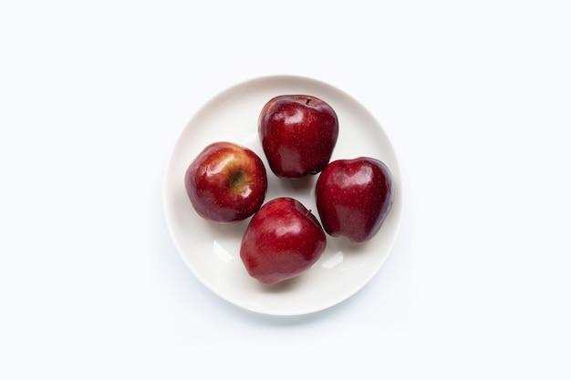 Verse rode appels in witte plaat op witte achtergrond. bovenaanzicht
