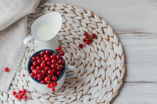 Verse rode bes en melk in een wit geëmailleerde metalen mok