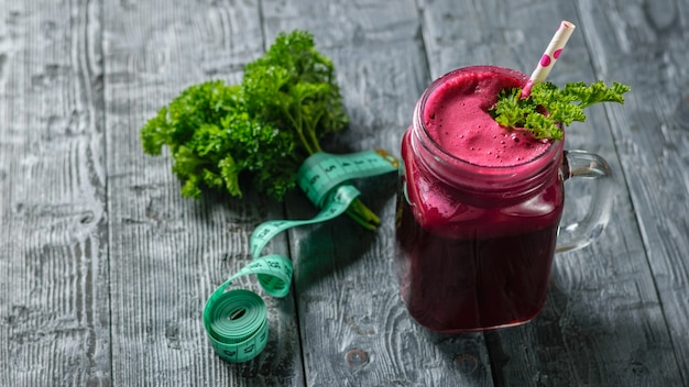Verse rode biet smoothie en metende tape en peterselie op zwarte houten tafel. het concept van natuurlijke voeding. vegetarische keuken. het uitzicht vanaf de top.