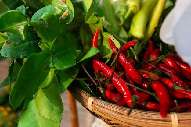 Verse rode chili en groene chili met limoenblad in bamboemand