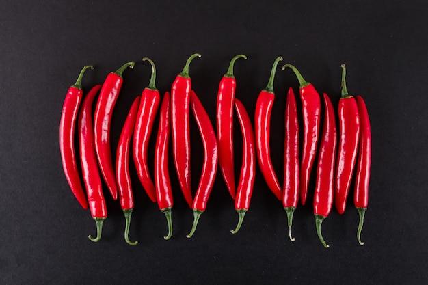 Verse rode chilipepers op zwarte ondergrond