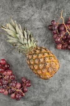 Verse rode druiven met rijpe ananas op marmeren oppervlak.